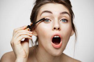 Mujer maquillando pestanas
